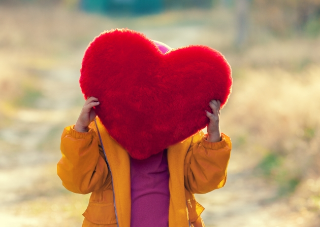 Little girl hiding behind heart shaped pillow and holding it in